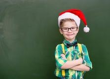 红色圣诞节帽子的微笑的男孩在一个绿色黑板附近 库存照片