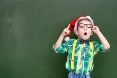 红色圣诞节帽子的惊奇的男孩在一绿色黑板showi附近 库存图片