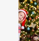 红色圣诞节帽子的愉快的女孩在白板后 te的空间 库存图片