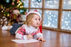 红色圣诞节帽子的逗人喜爱的女孩写信的给圣诞老人 免版税库存图片