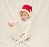 红色圣诞节帽子的逗人喜爱的小女孩 库存图片