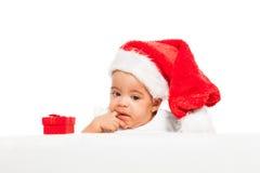 戴红色圣诞节帽子的非洲婴孩paci手指 免版税图库摄影