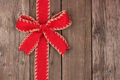 红色圣诞节弓和丝带旁边边界在老木头 免版税库存图片