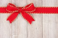 红色圣诞节弓和丝带顶面边界在老白色木头 免版税库存照片