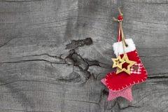 红色圣诞节或圣诞老人起动在一木老破旧乡村模式 库存照片