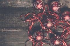 红色圣诞节球和丝带在木背景 invitation new year 框架 顶视图 复制空间 被定调子的照片 免版税库存图片