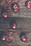 红色圣诞节球和丝带在木背景 invitation new year 框架 顶视图 被定调子的照片 免版税库存照片