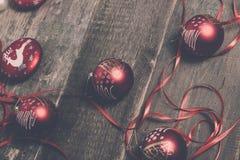红色圣诞节球和丝带在木背景 invitation new year 框架 顶视图 被定调子的照片 免版税图库摄影