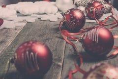 红色圣诞节球和丝带在木背景 invitation new year 被定调子的照片 免版税库存照片