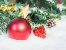 红色圣诞节球和箱子在雪 为后面复制和插入 免版税库存照片