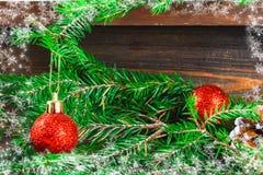 红色圣诞节球和锥体在冷杉分支围拢的一个木棕色架子说谎 免版税库存照片