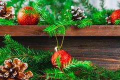 红色圣诞节球和锥体在冷杉分支围拢的一个木棕色架子说谎 库存照片