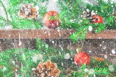 红色圣诞节球和锥体在冷杉分支围拢的一个木棕色架子说谎 免版税库存图片