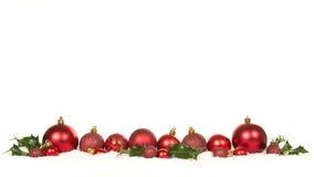 红色圣诞节球装饰和绿色霍莉冬青属行在雪 免版税库存照片
