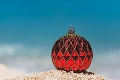 红色圣诞节球,冬天Holi特写镜头在热带海滩的 库存照片