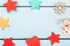 红色圣诞节的装饰,黄色星、天使、雪花和心脏在浅兰的木背景 复制您的文本的空间 能 库存图片