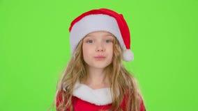 红色圣诞节盖帽的孩子女孩送空气亲吻 绿色屏幕 股票视频