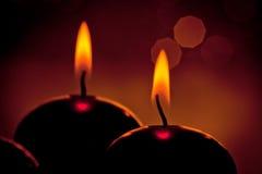 红色圣诞节蜡烛剪影在金黄bokeh背景的 库存照片