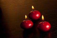 红色圣诞节蜡烛看法上面在温暖的色彩光背景的 免版税库存图片