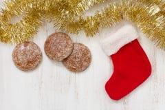 红色圣诞节袜子用在白色背景的曲奇饼 免版税图库摄影