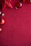 红色圣诞节装饰星和球在红色帆布背景 圣诞快乐看板卡 免版税库存图片