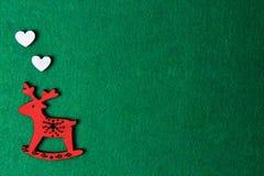 红色圣诞节鹿雕刻了在绿色背景的椅子,木eco装饰,玩具 图库摄影