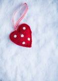 红色在冷淡的白色雪冬天背景的玩具和蔼心脏 爱和圣华伦泰概念 库存图片