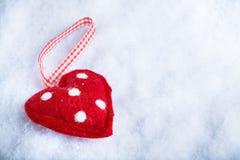 红色在冷淡的白色雪冬天背景的玩具和蔼心脏 爱和圣华伦泰概念 免版税库存照片
