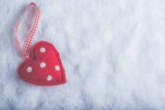 红色在冷淡的白色雪背景的玩具和蔼心脏 爱和圣华伦泰概念 免版税库存照片