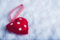 红色在冷淡的白色雪背景的玩具和蔼心脏 爱和圣华伦泰概念 库存图片