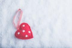 红色在冷淡的白色雪背景的玩具和蔼心脏 爱和圣华伦泰概念 库存照片