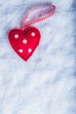 红色在冷淡的白色雪背景的玩具和蔼心脏 爱和圣华伦泰概念 免版税库存图片