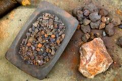 红色在地面上的被击碎的铁矿 免版税库存照片