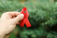 红色在手中援助丝带在绿色背景, HIV 库存照片