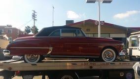 1950红色在拖曳的卡迪拉克汽车 卡车 免版税库存照片