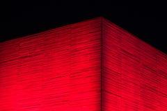 红色在晚上照亮了野兽派大厦混凝土墙  免版税图库摄影