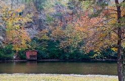 红色在池塘银行流洒了有秋天颜色的 库存图片
