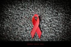 红色在石头的丝带红色丝带,世界援助天概念 免版税库存图片