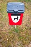 红色在绿色草坪的狗废物箱在公园区。 免版税库存图片