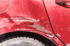 红色在街道抓了有损坏的油漆的汽车在崩溃事故或碰撞在停车场在城市 免版税库存照片
