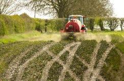 红色在领域的拖拉机传播的传播的泥浆 免版税库存图片