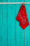 红色垂悬由在古色古香的小野鸭蓝色背景的绳索的班丹纳花绸和钥匙 免版税库存图片