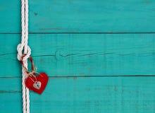 红色垂悬从绳索的心脏和锁由古色古香的蓝色木背景打结边界 库存图片