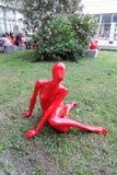红色塑料妇女雕塑 背景开花的结构树 库存图片