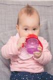从红色塑料瓶的女婴饮用水 库存照片