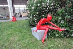 红色塑料womae雕塑 背景开花的结构树 库存图片