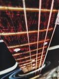 红色声学吉他关闭在黑暗的背景中 免版税库存图片