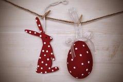 红色复活节兔子和垂悬在与框架的线的复活节彩蛋 库存照片