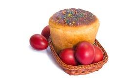 红色复活节彩蛋和复活节面包在一个篮子在一白色backgrou 免版税库存图片