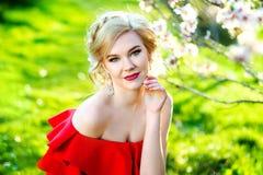 红色夏天礼服的年轻美丽的时髦的女孩走和摆在树之间的在胡同 免版税图库摄影
